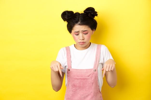 グラマーな明るい化粧をした悲しい惨めな女の子、見下ろして動揺し、悪いことを示し、黄色に立ち向かいます。