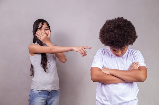 A sad moment of intimidation of a black boy being bullied. girl laughing making fun of the boy