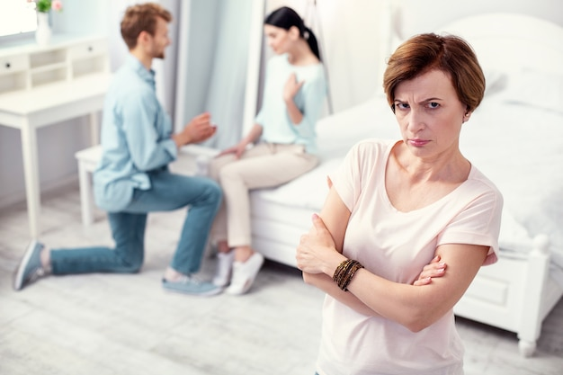 Sad mood. cheerless aged woman feeling depressed while thinking about her son and his girlfriend