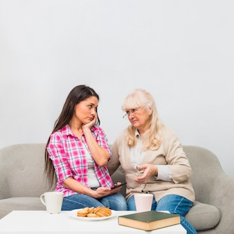 Sad mother and daughter looking at each other with breakfast on white table