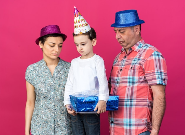 Sad mother and father with party hats looking at their disappointed son holding gift box isolated on pink wall with copy space