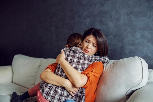 彼女の最愛の娘を抱き締める悲しい母親。彼女の母親を慰める娘。