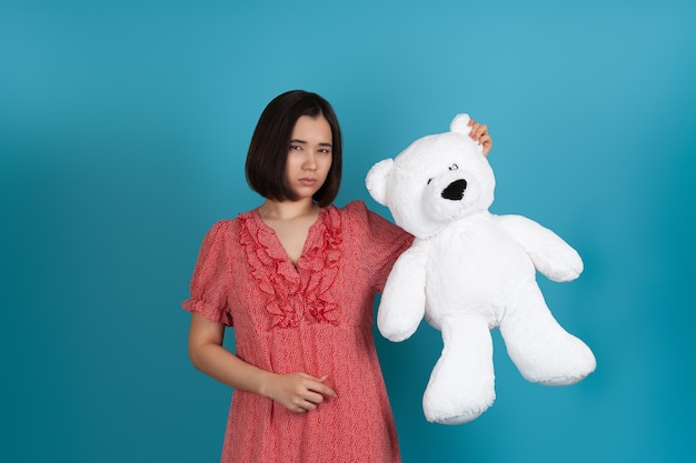 Sad offended disappointed woman in a red dress holding a white teddy bear by the ear