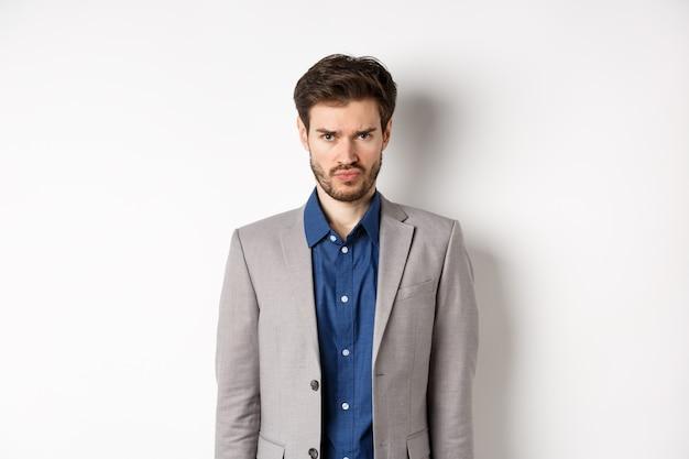 비즈니스 정장을 입고 찡그린 슬픈 불쾌한 남자는 흰색 배경에 대해 유치하게 서있는 불공평 한 것을 느낍니다.