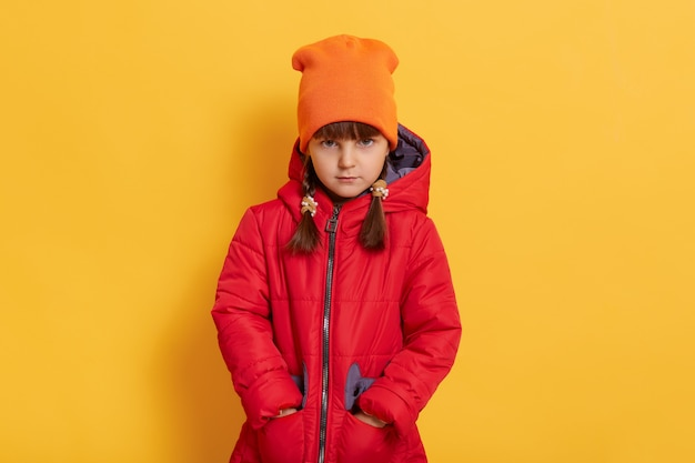 Sad offended little girl wearing orange cap and red jacket standing against yellow wall and looks at front with upset facial expression