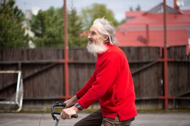 빨간 스웨터를 입고 자전거를 타는 슬픈 수염 난 남자, 바람에 나부끼는 머리카락