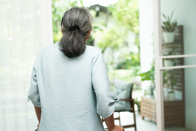 A sad old elderly woman uses walker for standing in front of windows and looking outside and feeling lonely.