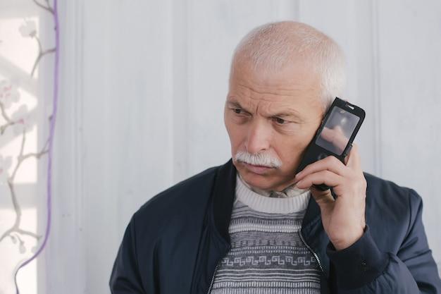 電話で悲しい老人。古いやシニアの男のコンセプトのデジタルテクノロジーとカジュアルなライフスタイル。