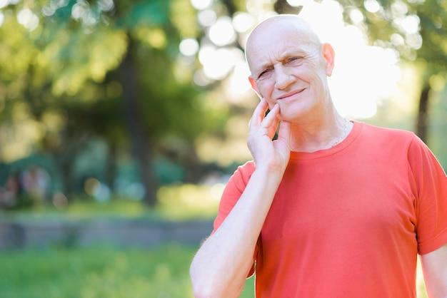 強い歯痛に苦しんでいる悲しい老人。頬に触れて痛みを感じる高齢者