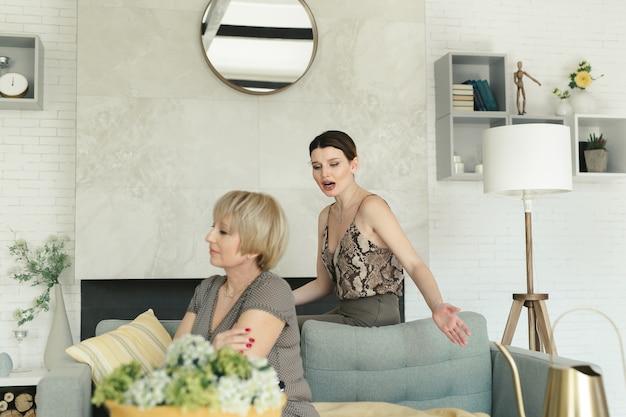 彼女の大人の娘が彼女に叫んでいる間、部屋のソファに座っている悲しい老婆