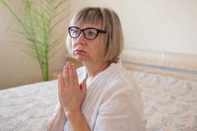 Грустная пожилая женщина молится богу с седыми волосами грустно в своей спальне в своем доме концепция одиночества