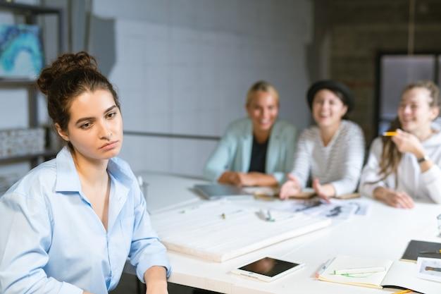 Грустная или задумчивая молодая студентка сидит за столом, пока ее друзья на заднем плане смеются над ней