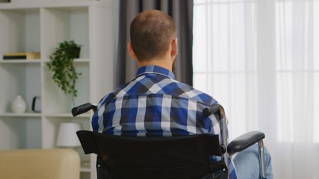車椅子に座っている悲しい麻痺した若い男。