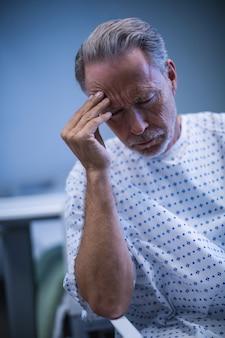 Грустный пациент сидит на стуле с рукой на голове