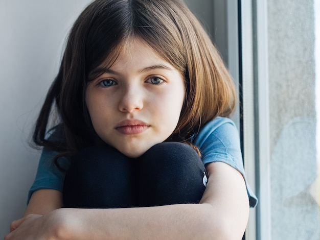 Sad pensive little girl sitting by the window