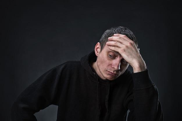 Sad pensive man with palm on his head