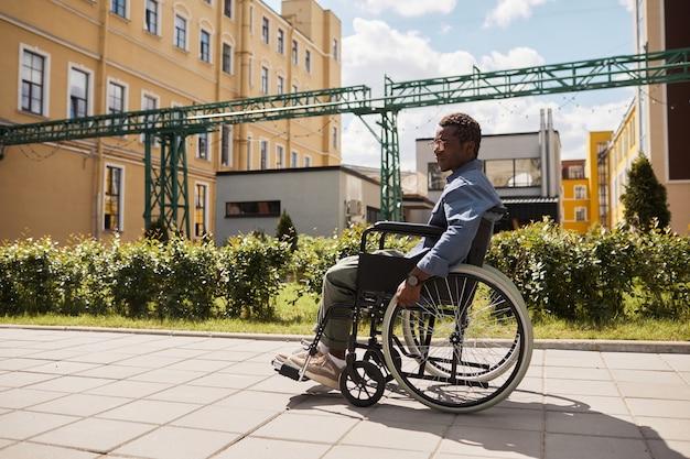 一人で通りを歩きながら車椅子を使用して眼鏡をかけた悲しい物思いにふける若い黒人障害者