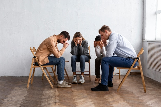 Sad people in chairs at a group therapy session