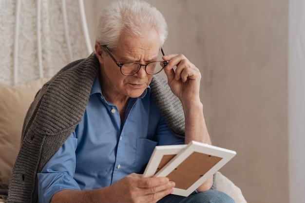 Грустно-пессимистичный старший мужчина поправляет очки и смотрит на фотографию, держа их