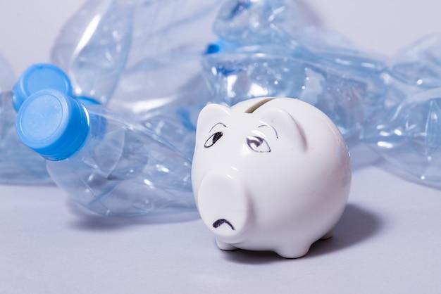 Грустная копилка и куча одноразовых мятых пластиковых бутылок
