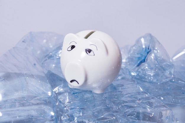 Sad piggy bank and bunch of disposable crumpled plastic bottles