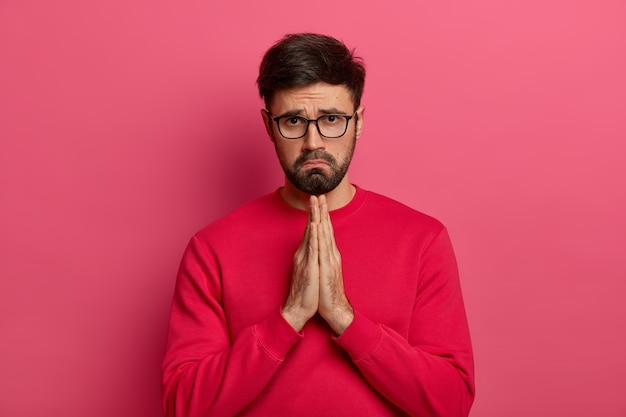 Sad pleading man says sincere please, makes praying gesture