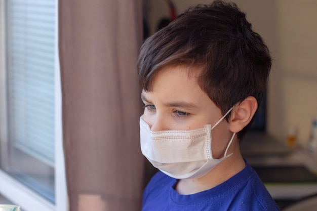 A sad portrait of a brunette boy in blue clothes and a white medical mask stands by the window.
