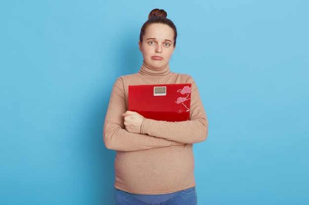 Грустная беременная женщина в бежевой водолазке обнимает напольные весы и смотрит прямо в камеру с надутыми губами, изолированными над синей стеной.