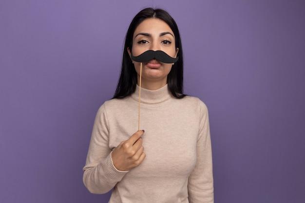 悲しいかなりブルネットの白人の女の子は紫の棒に偽の口ひげを保持します