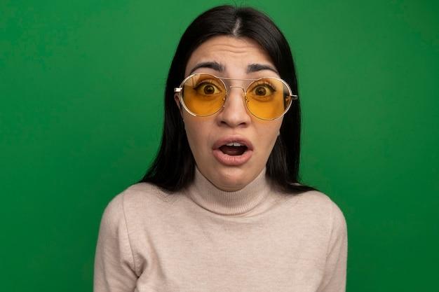 緑のカメラを見てサングラスで悲しいかなりブルネットの白人の女の子