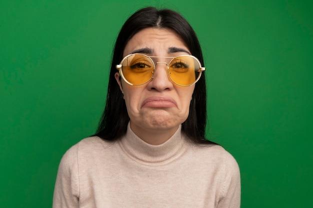 La ragazza caucasica abbastanza mora triste in occhiali da sole esamina la macchina fotografica sul verde