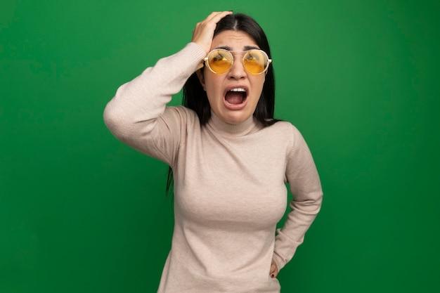 Ragazza caucasica abbastanza mora triste in occhiali da sole mette la mano sulla testa e guarda in alto sul verde