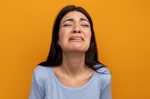 La donna graziosa del brunette triste esamina la parte anteriore isolata sulla parete arancione