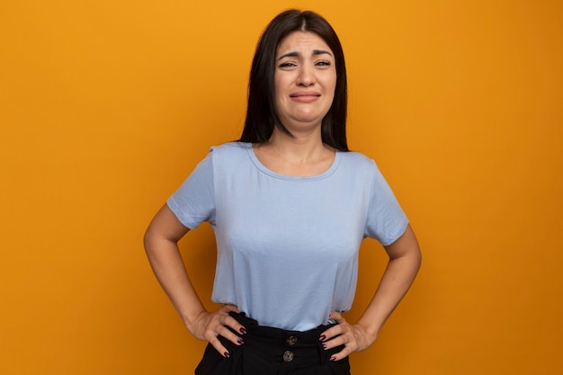 Sad pretty brunette woman puts hands on waist and looks at front isolated on orange wall