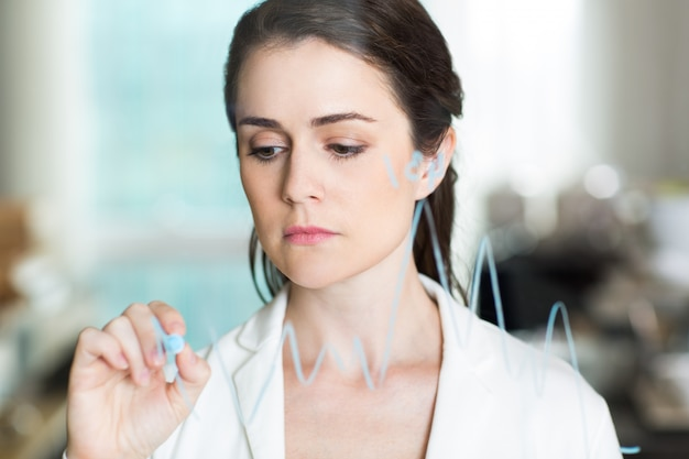 Sad pretty businesswoman drawing graph on glass