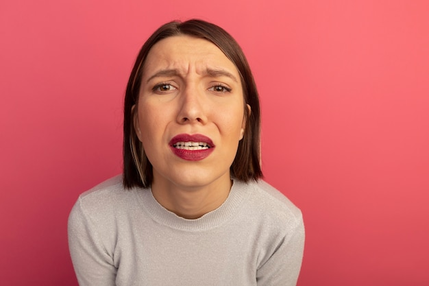 Sad pretty woman looks at front isolated on pink wall