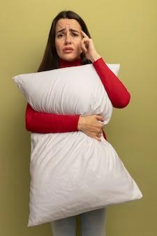 La donna graziosa triste mette la mano sul viso e tiene il cuscino isolato sulla parete verde oliva