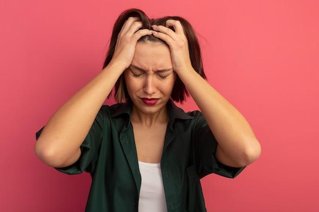 Грустная красивая женщина кладет руки на голову и делает вид, что плачет, изолирована на розовой стене