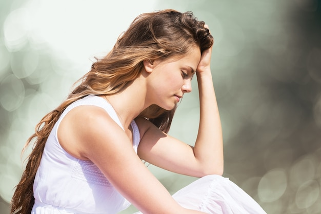 Sad pretty woman sitting holding head with hand on background