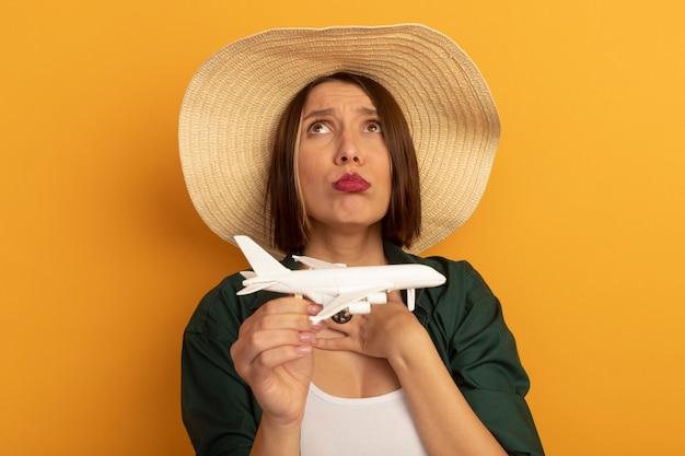 Triste bella donna con cappello da spiaggia tiene aereo modello e guarda in alto isolato sulla parete arancione
