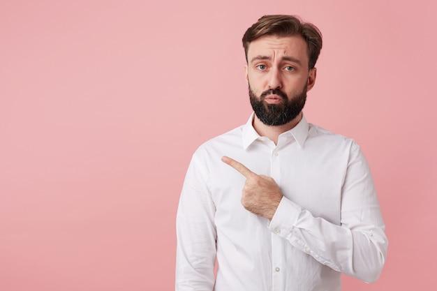 ピンクの壁にトレンディな髪型を身に着けているひげを持つ悲しいかなり若いブルネットの男性、動揺した顔と眉をひそめている正面を見て、人差し指で脇に表示