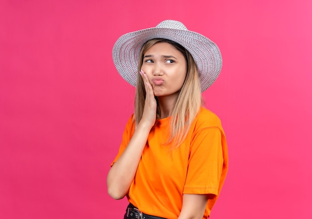 A sad pretty young woman in an orange t-shirt wearing sunhat keeping hand on her teeth while having ache on a pink wall