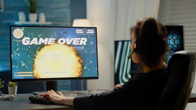 Грустная профессиональная женщина-геймер с гарнитурой проигрывает видеоиграм, транслирующим космический шутер из игровой студии. игра окончена для кибер-игрока, участвующего в онлайн-соревнованиях по киберспорту на мощном компьютере