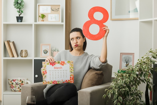 Guance gonfie tristi bella ragazza in una felice giornata delle donne che tiene il numero otto con il calendario seduto sulla poltrona in soggiorno