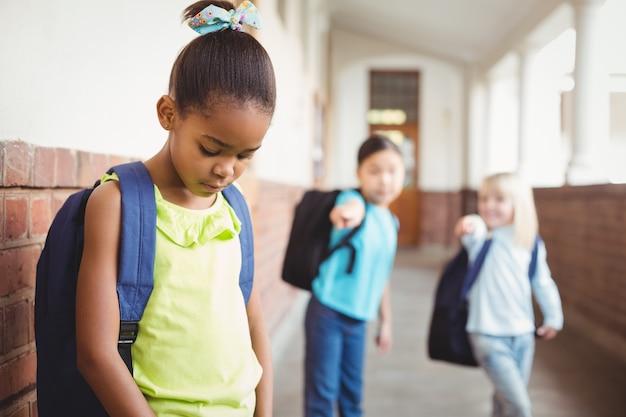 悲しい生徒が廊下の同級生に脅迫されている