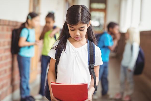 Sad pupil being bullied by classmates at corridor Premium Photo