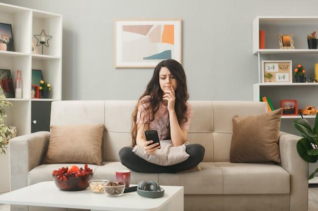 Грустно прикладывая палец к губам, молодая девушка держит телефон, сидя на диване за журнальным столиком в гостиной