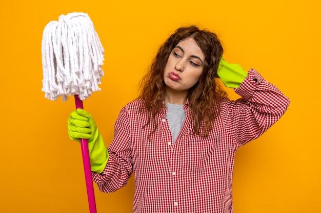 Triste mettendo la mano sulla testa giovane donna delle pulizie che indossa guanti tenendo e guardando mop
