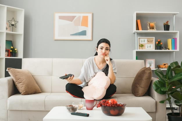 Грустно положив руку на щеку, молодая девушка с подушкой держит телефон, сидя на диване за журнальным столиком в гостиной