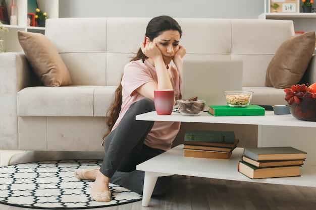 悲しい頬に手を置く若い女の子は、リビングルームのコーヒーテーブルの後ろの床に座っているラップトップを使用しました